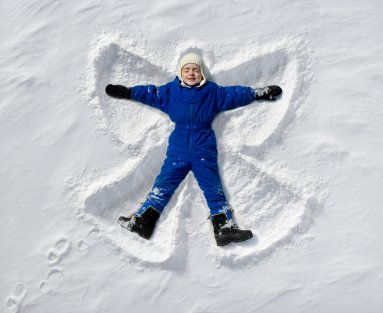 Child in snow making snow angel