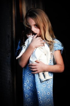 girl hiding behind her doll